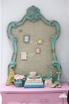 Love everything here! Wonderful pink dresser, shabby turquoise mirror turned bulletin board, gold sequined letter, metallic turquoise candlesticks, and bunting with little picture frames on the bulletin board.