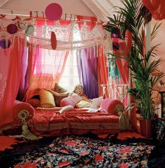 Lots of pillows, sheer curtains, and shawls draped across the floor and hanging over the bed in this Bohemian bedroom.