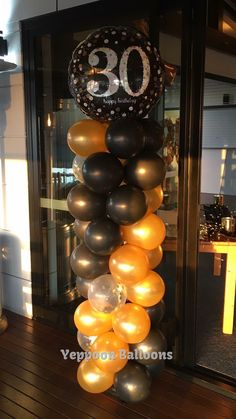 """Black, gold and confetti balloon column with 36"""" foil topper."""