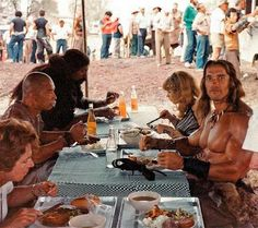 Arnold Schwarzenegger and Wilt Chamberlain having lunch with the rest of the cast on the set of Conan the Destroyer.