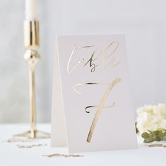 These Ginger Ray Metallic Gold Tented Table Numbers feature the numbers 1 through 12 printed on them in metallic gold script. Place these gold foil cardstock table numbers with other metallic gold table decorations! Rustic Table Numbers, Wedding Table Numbers, Wedding Table Number Holders, Table D'or, Baby Shower Party Deko, Table Rose, Card Table Wedding, Wedding Tables, Tent Cards