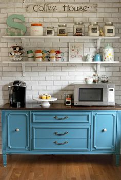 Create your own coffee bar by moving the coffee maker, mugs, and beverage add-ins to a sideboard or vintage buffet as shown (scored from Craigslist!) for a better traffic pattern in the kitchen.