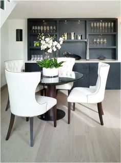 White Black Chic Dining Room Design With Tufted Chairs Nailhead Trim Glass Top Round Table Wood Base And