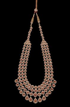 [REVERSE] A diamond-set enamelled gold Necklace India, Jaipur, 20th century comprising three rows of circular diamonds set in gold, terminating in a single row of diamonds, larger teardrop shaped diamonds suspended below, verso enamelled in polychrome with floral design 23 cm. long