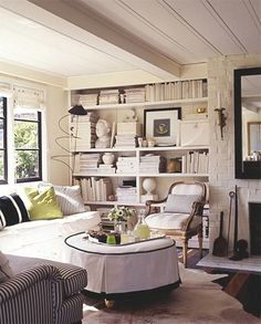 I like the painted brick fireplace with painted ceiling paneling and walls and bookshelves.   Love the group of seating and cowhide on floor. The graphic back frame mirror is great on the white crisp wall.