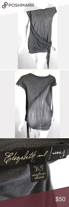 Elizabeth & James Gray Faux Wrap Top Sheer Panel Elizabeth & James  Size: XS (seems to run big, could fit bigger sizes too) Color: Gray Style: Faux Wrap Top  Condition: Pre-Owned Gently Worn No Flaws  Features:  -Pull Over Styling -90% Modal, 10% Cashmere -Short/ Cap Sleeves -Sheer Back Panel -Raw Edge Seams  Measurements taken while garment was laying flat: These measurements were personally taken and are approximate:  Underarm to Underarm inches- 22 Length from shoulder seam to hem inches…