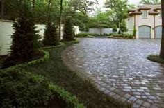 A paver driveway is one of the most durable and attractive additions you can have added to your landscape master plan.  Due to the sheer number of paver types, their use is not limited to one particular type of landscape design.    While many are distinctively Old World and early 20th Century in appearance, others can be cast to emulate stone or concrete forms more apropos to modern landscaping and contemporary landscapes.  Pavers are cast masonry blocks that are geometrically shaped, very resil