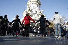 【2015.11.16 月曜日】【写真特集】犠牲者への追悼続く、パリ連続襲撃×仏パリ連続襲撃事件の犠牲者を悼み、レピュブリック広場に集まって手をつないだ人たち(2015年11月15日撮影)。(c)AFP/PATRIK KOVARIK