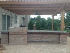 Brick patio with outdoor kitchen and pergola