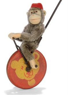 A STEIFF PUSH-A-LONG FLINKO, (322), brown mohair chimpanzee, brown and black glass eyes, pink felt face, ears, hands and feet, swivel head, jointed, red felt fez and FF button, seated on a wire and wood unicycle, the red wheel stencilled with a yellow Teddy Bear head, circa 1927 --27in. (68.5cm.) high (fading and some wear)