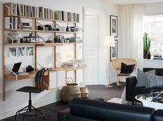 Bambuhyllor på väggen i ett vardagsrum i mörkbrunt, svart och vitt.