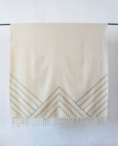 Mexchic Stella Lines Embroidered Blanket in Triangle I Remodelista The Stella Lines Embroidered Blanket in Triangle, $300, is hand-loomed and embroidered by women in Malinalco. The limited-edition design is inspired by the work of painter Frank Stella and ancient Aztec and Mayan grecas. The blankets come in a choice of cream or gray, with embroidery in olive (shown), cream, gray, or black.
