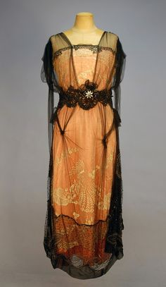 BEADED NET, SILK and LACE DINNER DRESS, 1912. Sleeveless Pink silk beneath cream net with floral embroidery, draped black tulle tabard decorated with black and crystal beads, silver sequins, tassels and a paste flowerhead.