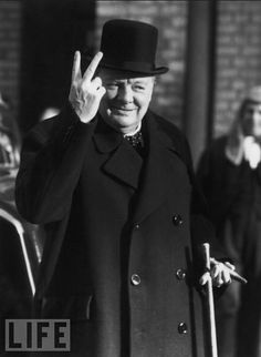"""Winston Churchill giving his signature """"V"""", which, given how it's facing, I imagine would mean both """"Victory"""" and something far ruder (aimed at the Axis)."""