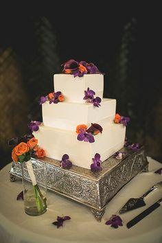 orange and purple wedding cakes | Wedding cake with orange and purple flowers.