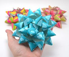 Make your own cool custom gift toppers with your favorite decorative wrapping paper and this easy-to-follow DIY paper gift bow tutorial!