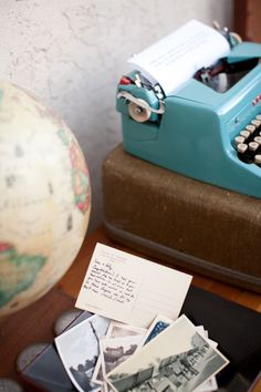 The vintage postcards are filled out by guests to function as the guest book. The globe echoes the traveling theme.