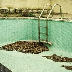 Old, empty, no longer used swimming pool, however, isn't that a noodle stuck behind the ladder?