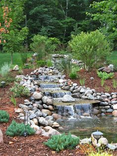 Stone borders and a simple but eye-pleasing flow of water through descending levels makes an ideal waterfall for backyards in this design by Miller Creek Lawn & Landscape.
