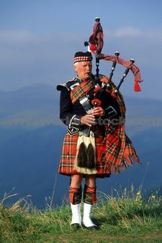 Bagpiper At Loch Broom In Scottish Highlands
