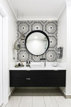 "In this Melbourne bathroom, a Moroccan inspired Schumacher wallpaper called Nasrid Palac Mosaic in Mica from Grant Dorman Interior Products tricks the eye into thinking it's resting on tiles. ""It's a hand-painted paper in black, white, gold and silver that ties the room together beautifully,"" says interior designer Teresa Kleeman of Embracing Space. The mirror is a masterful match for it. *Photograph by Tahnee Jade.*"