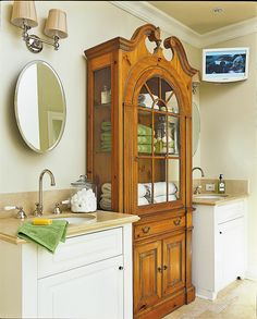 A treasured antique hutch was incorporated into this master bath as a linen cupboard.