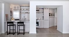 Designer Joseph Lembo's Apartment Renovation: Lembo chose Caesarstone for the full-height backsplash, and the counters were all done by Euro Custom Woodworking, Inc. The kitchen stools are from BDDW. Benjamin Moore's Winter Orchard paint No. 1555 covers the entire apartment, except for the new powder room.
