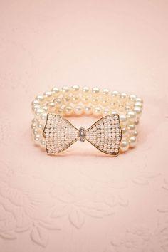 Avec cette boucle en or ornée de diamants, complétée par un délicat assemblage de perles, vous serez la reine. This golden bow, ornate with three diamonds, on top of a delicate mounting of pearls, will make you a queen.