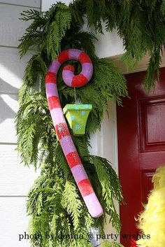 Candy Cane on porch Dollar store pool noodle, wire hanger, paint and glitter. Make for less than $2