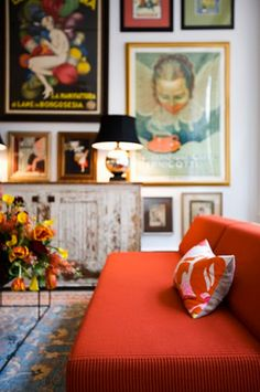 orange sofa, fresh flowers, old patina console, art gallery wall