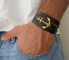 "Men's Bracelet - Black Leather Bracelet With Gold Plated Anchor - Mens Jewelry - Nautical Jewelry - Anchor Jewelry  Looking for a gift for your man? You've found the perfect item for this!   The simple and beautiful bracelet combines black leather which wrap 3 times on hand and a gold plated anchor pendant with a khaki-colored wire wrapped on it.  Lengh: 22.8 (53 cm) + 2"" (5 cm) extension chain.  $37"