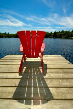 on a muskoka chair on a sunny day near the water
