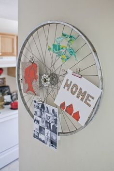 An old bicycle wheel on the wall to hold pictures, cards, etc.