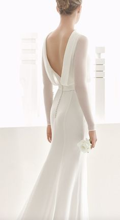 Sleek long-sleeve white wedding dress with low draped back design; Featured Dress: Rosa Clara