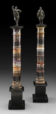 An impressive pair of blue john columns possibly English first half 19th century Each, now surmounted by a bronze figure, probably depicting Julius Caesar and Marc Antony, the ring turned slightly tapered columns, raised on square black slate plinths. height of column 20 1/4in