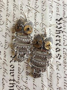 These silver tone jointed owl earrings are gorgeous!Not only will they add a touch of Steampunk to any outfit, but they add movement to your outfit, drawing the eye of people.People won't be able to take their eyes off you!These can be replicated, but each pair will vary slightly. Vintage clockwork parts are used for the eyes, and the varying placement of these make each piece completely unique.