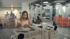 Day in Office with Multi-ethnic Employees by Pressmaster Lockdown of people working in modern office with glass walls: attractive Asian businesswoman putting paper into printer, African businessman and Caucasian male colleagues working in background