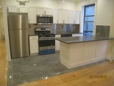 "Amazing kitchen remodel using Stainless Steel 1""x3"" backsplash tile, pair perfect with appliances and the grey flooring and countertops."