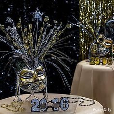 Accessories + Decoration = 2016 Masquerade centerpiece! To put this together all you'll need are beads to fill a candy container, a spray centerpiece and a mask of your choice.