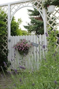 White picket garden gate with arbor and a flower basket!