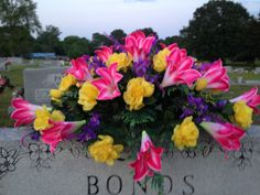 Silk tomb topper using pink lilies, yellow roses and purple filler. May 2015