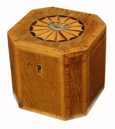 A George III rosewood and satinwood octagonal tea caddy, with stringing, the hinged top with a circular patera and a Sheffield plate ring handle revealing a mahogany cover, 5in (12.5cm) h, 5.25in (13.5cm) w.   Woolley & Wallis