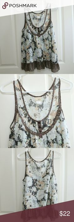Buckle Daytrip Blouse Tank Floral Ruffles Size M Buckle brand Daytrip.  Blouse / Tank / Sleeveless.  Neutral floral pattern.  Sheer.  Ruffle at hem.  Size Medium.  About 17 inches armpit to armpit.  About 25 inches shoulder to hem.  NWOT.  No wear, no flaws. Daytrip Tops Blouses