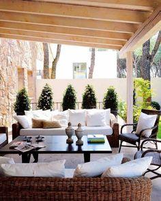 rustikal einladend moderne Terrassengestaltung Korbmöbel weiße Auflagen Deko Kissen viel Grün