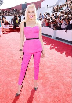 Gwen Stefani rocking the red carpet in a bright pink peplum top and matching pants.