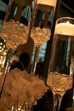 Champagne flutes are the perfect vessel for floating candles as a centerpiece!