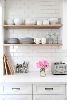 """""""My kitchen is a very white-- and I love it-- but to keep it from feeling too cold and clinical I added some natural wood.  These natural wood shelves turned out to be my absolute most favourite part of the kitchen. The[y] hold all of my everyday dishes and glassware.  … everything gets stacked right up on these shelves and is used every, every day.""""--Elissa"""