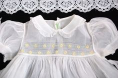 What a beautiful Easter dress this would be! It is a true vintage dress made by Feltman Brothers in the Philippines....love this one!  Dress is white 100% cotton organdy with yellow & green embroidered daisies across the bodice and skirt.  Peter pan collar and puffed sleeves are edged in tiny cotton lace..so sweet.  Dress has a very deep 5 hem....beautiful detail.  This is an heirloom dress for your baby or lovely for dressing your doll.    The dress is in Excellent condition with No stai...