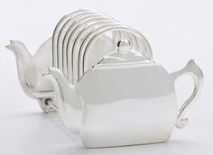 "Nickel-plated zinc alloy teapot motif toast rack. Measures 3 ½"" high by 5 ½"" wide. This item compliments our napkin holder"