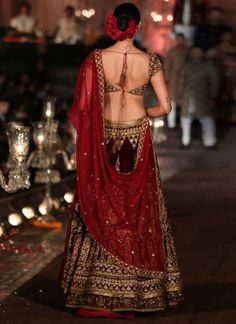 This maroon color lehenga is in velvet fabric with net dupatta. Lehenga skirt and blouse are beautifully crafted in hand embroidery with dabka, nakshi and zardozi. Dupatta is in net fabric with four sided zardozi borders and butties inside the dupatta. Indian Wedding Gowns, Luxury Wedding Dress, Indian Dresses, Indian Outfits, Indian Clothes, Indian Weddings, Wedding Attire, Wedding Lehanga, Saree Wedding